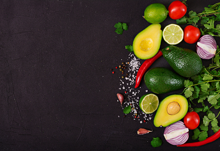 Guacamole sauce ingredients - avocado, tomato, onion, pepper chili, garlic, cilantro, lime on black background. Top view