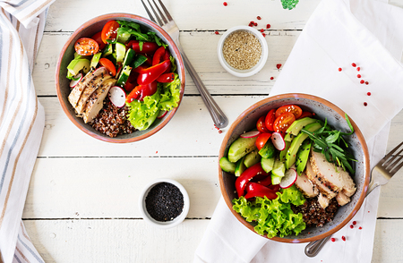 Photo for Buddha bowl dish with chicken fillet, quinoa, avocado, sweet pepper, tomato, cucumber, radish, fresh lettuce salad and sesame. Detox and healthy superfoods bowl concept. Overhead, top view, flat lay. - Royalty Free Image