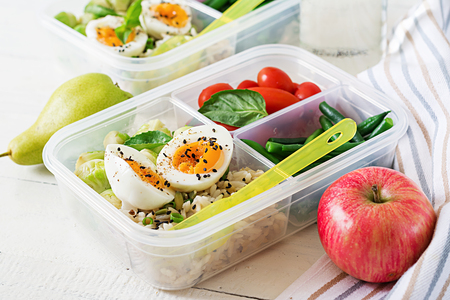 Foto de Vegetarian meal prep containers with eggs, brussel sprouts, green beans and tomato. Dinner in lunch box - Imagen libre de derechos