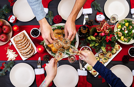 Foto de Baked turkey. Christmas dinner. The Christmas table is served with a turkey, decorated with bright tinsel and candles. Fried chicken, table.  Family dinner. Top view - Imagen libre de derechos