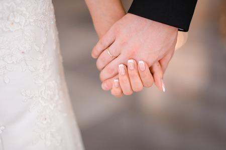 Photo pour Bride and groom holding hands outdoors - image libre de droit