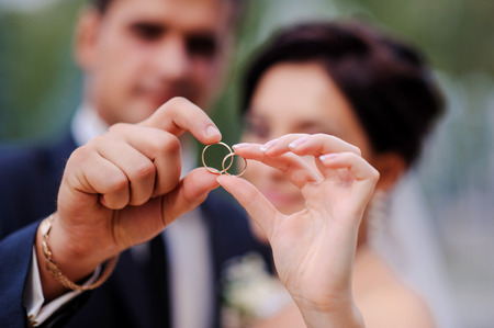 Photo pour bride and groom holding hands in a ring - image libre de droit