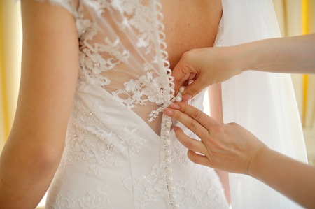 Photo for Bridesmaid is helping the bride to dress. - Royalty Free Image