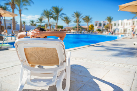 Photo for woman lying on a lounger by the pool at the hotel. - Royalty Free Image