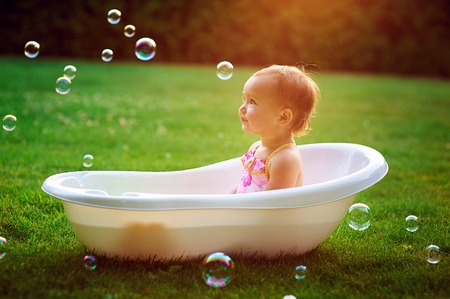 Foto de little girl bathes in a bath with soap bubbles. - Imagen libre de derechos