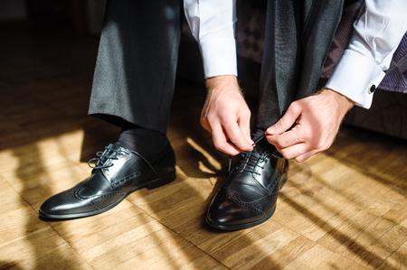 Foto de Business man tying shoe laces on the floor. Close-up. - Imagen libre de derechos