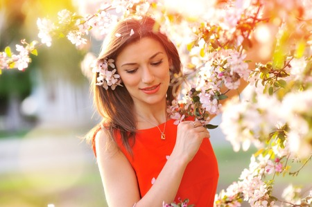 Beautiful Spring woman with blossoming flowers on trees in garden.
