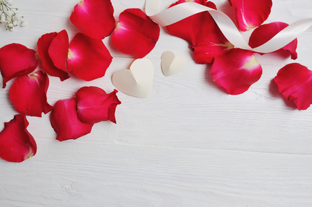 Photo pour Mockup Rose petals with two white hearts on a white wooden background, card Valentines Day. Flat lay, top view with a place for your text - image libre de droit