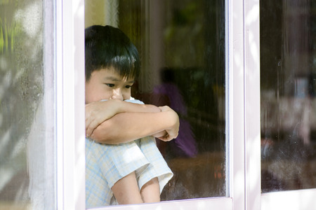 Asian boy sit beside window after rain at home look sad and lonely concept.
