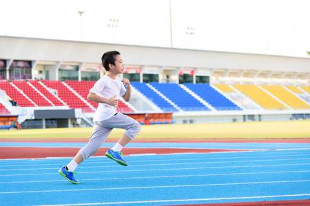 Foto de Young Asian boy running on blue track in the stadium during day time to practice himself. - Imagen libre de derechos