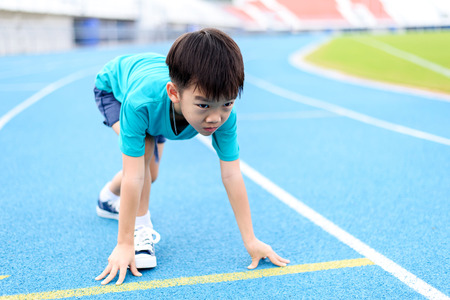 Photo pour Young Asian boy prepare to start running on blue track in the stadium during day time to practice himself. - image libre de droit