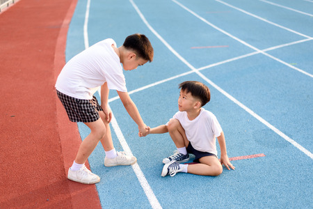 Photo pour Young asian boy give hand to help accidented boy during running on the blue track. - image libre de droit