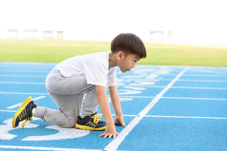 Photo pour Young Asian boy running on blue track in the stadium during day time to practice himself. - image libre de droit