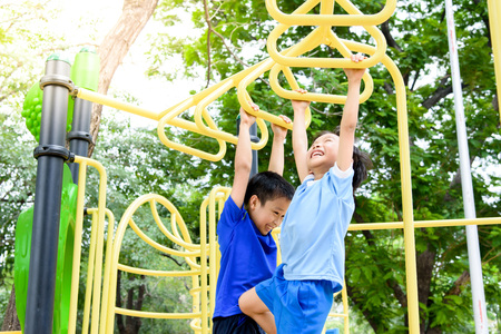 Photo pour Young asian boy hang the yellow bar by his hand to exercise at out door playground under the big tree. - image libre de droit