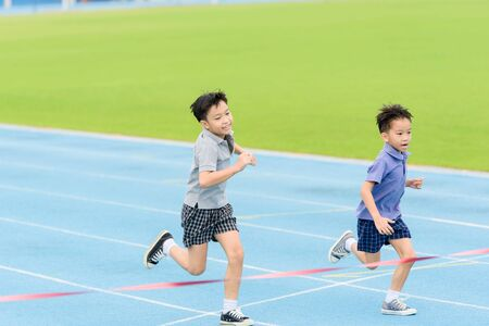 Photo pour Selective focus at young Asian boy running on blue track to the finished line. - image libre de droit
