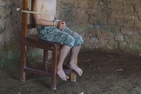 Foto de Victim boy with hands tied up with rope in emotional stress and pain,  kidnapped, abused, hostage,  afraid, restricted, trapped, pitiable,  struggle,  Stop violence against children and trafficking Concept. - Imagen libre de derechos