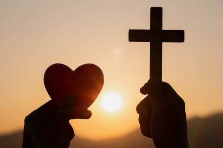 Photo pour Silhouette of woman hands praying with cross and holding a red heart ball  in nature sunrise background,  Crucifix, Symbol of Faith. Christian life crisis prayer to god, The concept of loving God. - image libre de droit