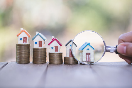 Foto de House searching concept with a magnifying glass, house and money. magnifying glass and coins. concept of mortgage, construction, rental housing. - Imagen libre de derechos