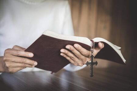 Photo for Human hand holds cross and bible, Worship, sins and prayer, Religious concept., Eucharist Therapy Bless God Helping Repent Catholic Easter Lent Mind Pray. - Royalty Free Image