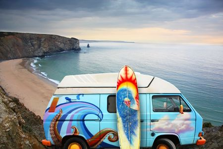 A blue van with a surf board at the beach