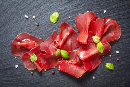 Photo pour Food appetizer concept Sliced Dried Cured beefs Bresaola on black slate stone board - image libre de droit