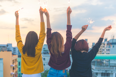 Foto de Outdoor shot of young people at rooftop party. Happy group of asia girl friends enjoy and play sparkler at roof top party at evening sunset. Holiday celebration festive party. Teenage lifestyle party. - Imagen libre de derechos