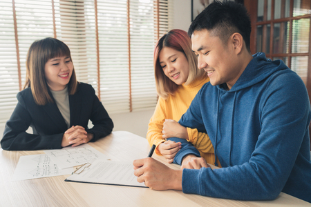 Foto de Happy young Asian couple and realtor agent. Cheerful young man signing some documents while sitting at desk together with his wife. Buying new house real estate. Signing good condition contract. - Imagen libre de derechos