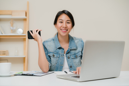 Photo pour Beautiful smart business Asian woman in smart casual wear working on laptop and talking on phone while sitting on table in creative office. Lifestyle women working at home concept. - image libre de droit