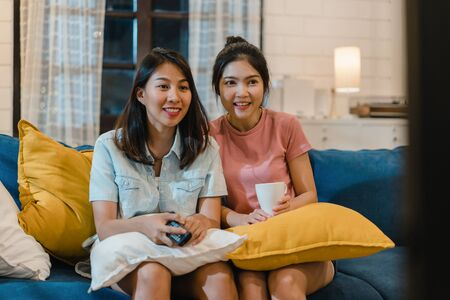 Foto de Lesbian lgbt women couple watching television at home, Asian female lover feeling happy funny moment looking drama entertainment together on sofa in living room in night concept. - Imagen libre de derechos