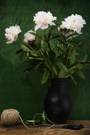 Foto de Still life- peony sprig of flowers in transparent glass jar - Imagen libre de derechos
