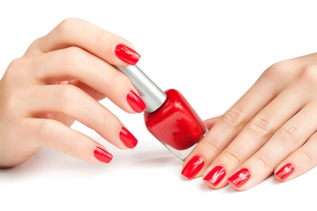 Hands with red manicure and nail polish bottle isolated