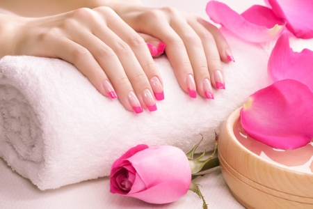 female hands with fragrant rose petals and towel