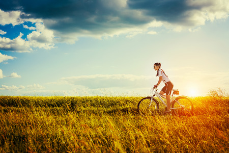 Photo for Young Woman is riding bicycle outside  Healthy Lifestyle - Royalty Free Image