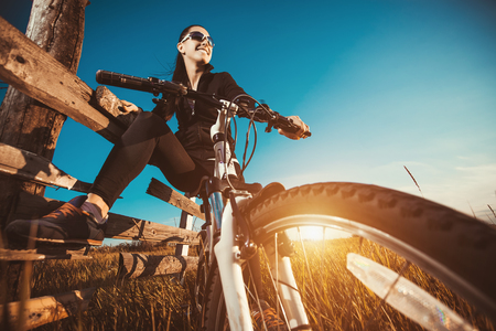 Photo pour Happy Young Woman riding bicycle outside. Healthy Lifestyle. - image libre de droit