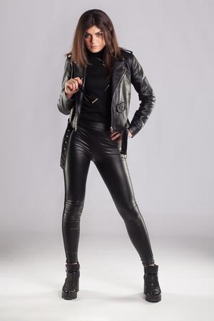 Foto de Young brunette lady in black leather jacket and pants posing on grey background - Imagen libre de derechos