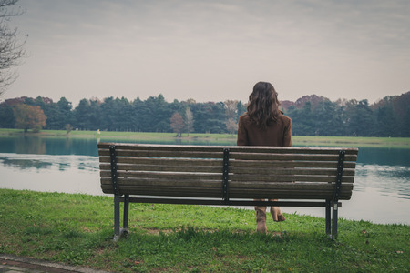 Photo for Beautiful young woman with long hair sitting on a bench in a city park - Royalty Free Image