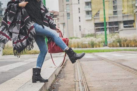 Foto de Detail of a young woman with poncho posing in the city streets - Imagen libre de derechos