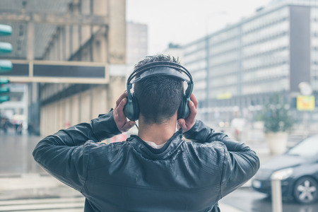 Photo for Back view of a young man with headphones listening to music in the city streets - Royalty Free Image