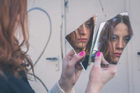Foto de Beautiful redhead girl with long hair and blue eyes looking at herself in a broken mirror - Imagen libre de derechos