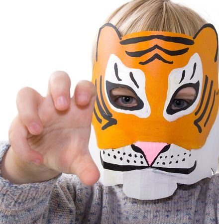 child with tiger mask. kid pretending to be wild animal. toddler dressed up playing and isolated on white