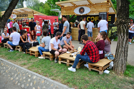 Foto de CLUJ-NAPOCA, ROMANIA - JULY 9, 2016: People have a snack at the Street Food Festival in central park Cluj. Vendors in stalls sell tasty fast food from different cultures. - Imagen libre de derechos