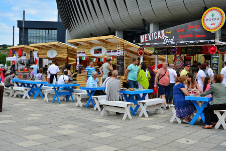 Foto de CLUJ-NAPOCA, ROMANIA - JULY 9, 2016: People have a snack at the Street Food Festival in front of the Cluj Arena stadium in central park Cluj. Vendors in stalls sell fast food from different cultures. - Imagen libre de derechos