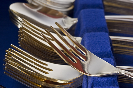 Closeup of a boxed set of gold plated flatware. Stacks of forks, spoons, and knives.