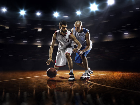 Photo pour Two basketball players in action in gym in lights - image libre de droit