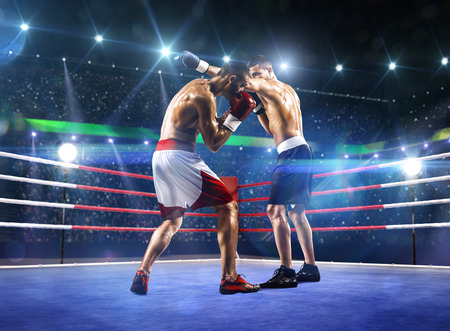 Photo pour Two professionl boxers are fighting on the grand arena - image libre de droit