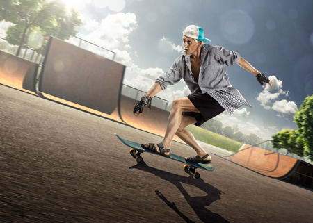 Foto per The old man is skating on skateboard in skate park - Immagine Royalty Free