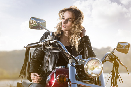 Foto de Biker girl in the  leather jacket on a motorcycle looking at the sunset. - Imagen libre de derechos
