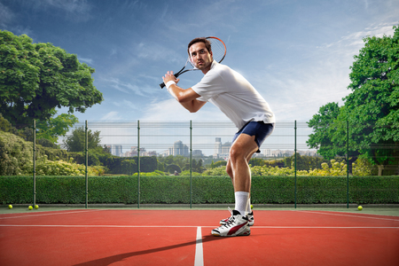 Photo pour Young man is playing tennis on sunny day - image libre de droit