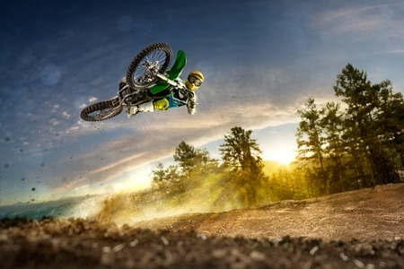 Photo pour Dirt bike rider is flying high in evening - image libre de droit