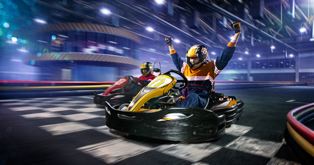 Photo for Two cart racers are racing on the grand track motion - Royalty Free Image